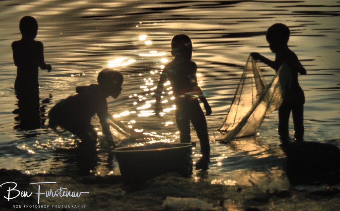 Sun reflections on kids net fishing in Chembe, Cape Maclear, Lake Malawi, Malawi