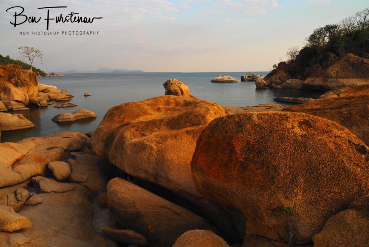 Calm waters over boulder shoreline looking south on Lake Malawi, Otter Point, Malawi