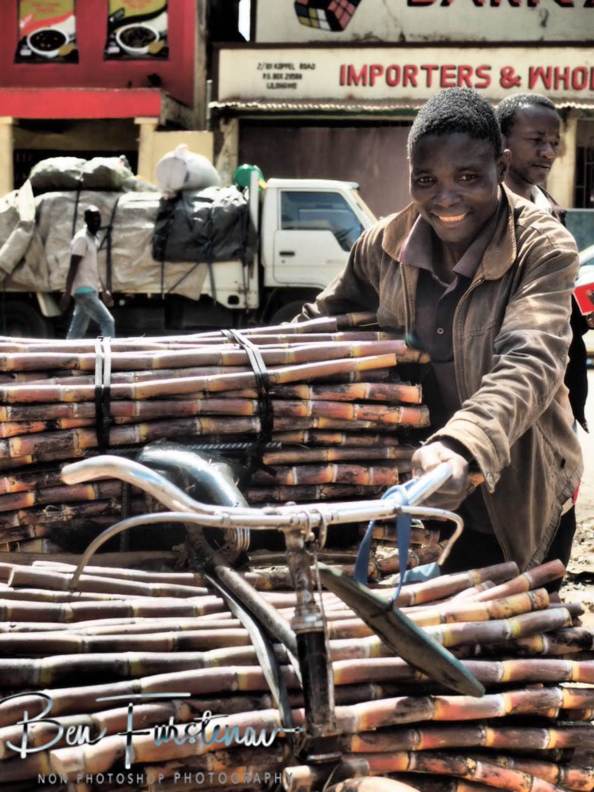 Trying to smile whilst pushing heavy load in Lilongwe, Malawi
