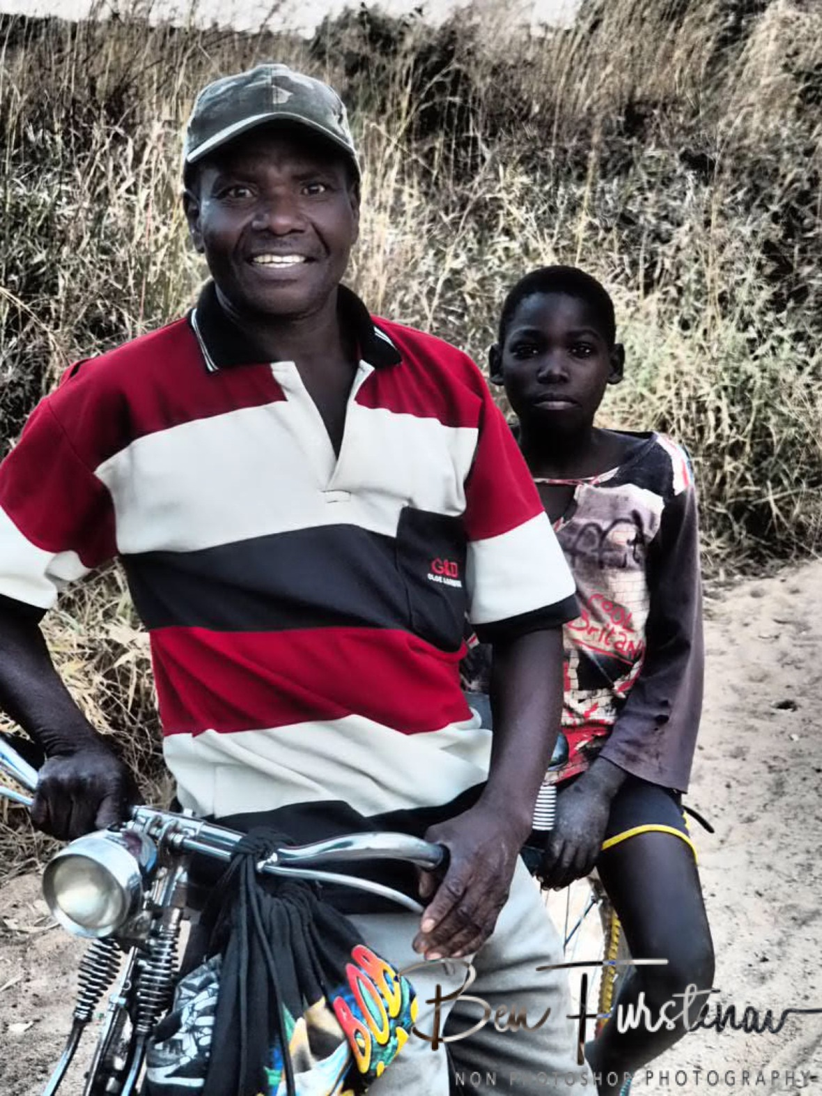 Father and son bike in Northern Region, Malawi