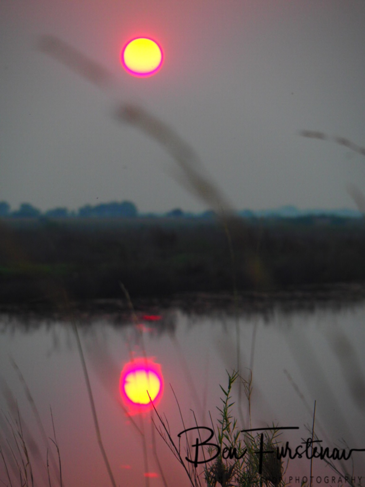 A purple ring appears around the yellow sun near Sioma Falls, Zambia
