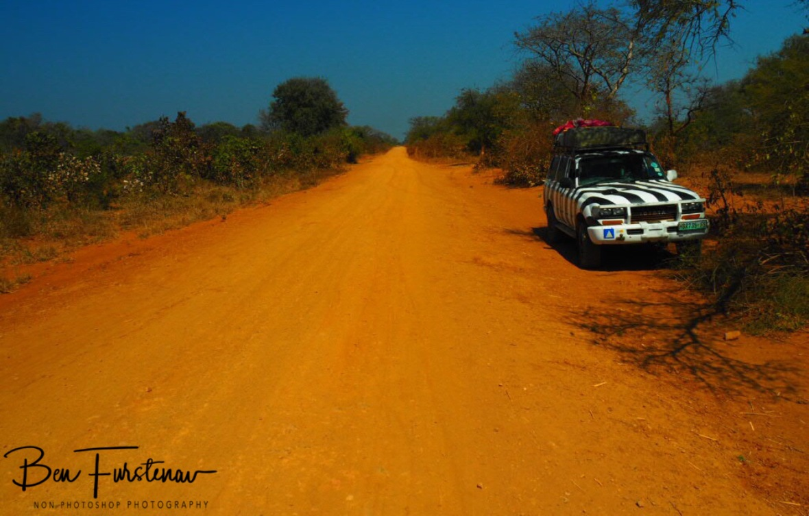 Straight red track in blue skies near Blue Lagoon National Park, Zambia