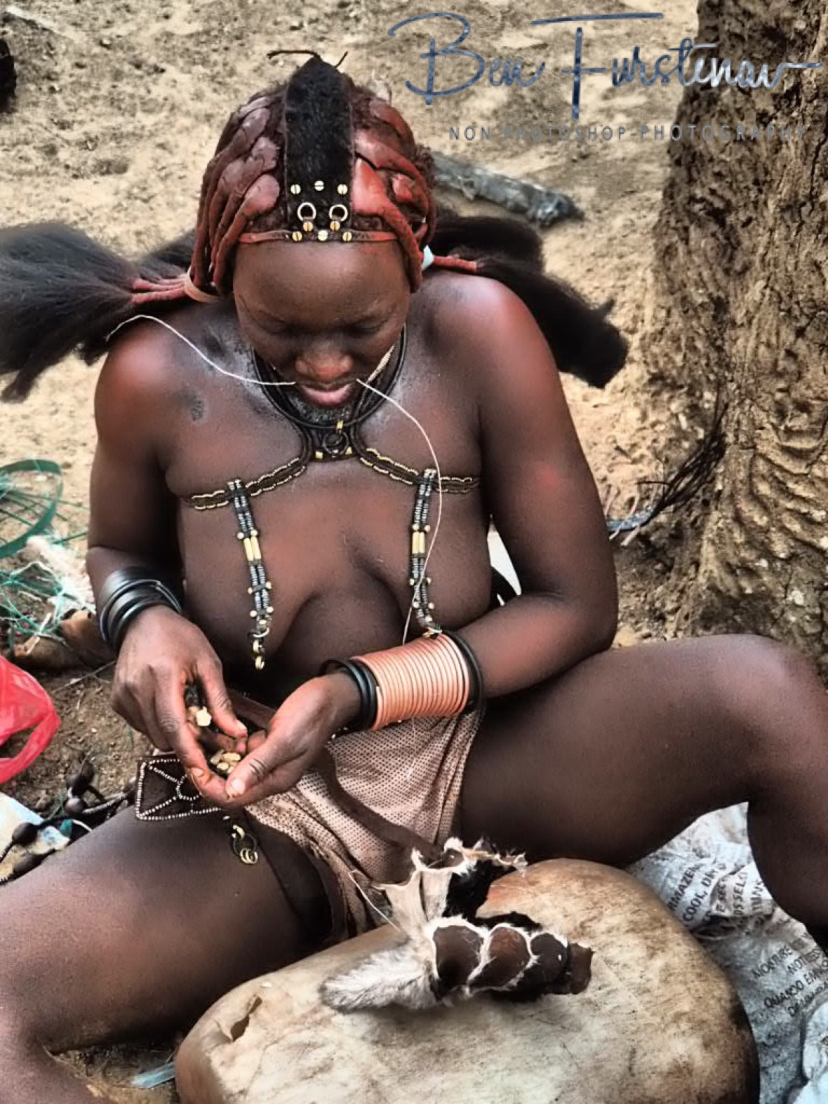 Placing stones to the hat to give it the horn shape, Omusaona Himba Village, Kamanjab, Namibia