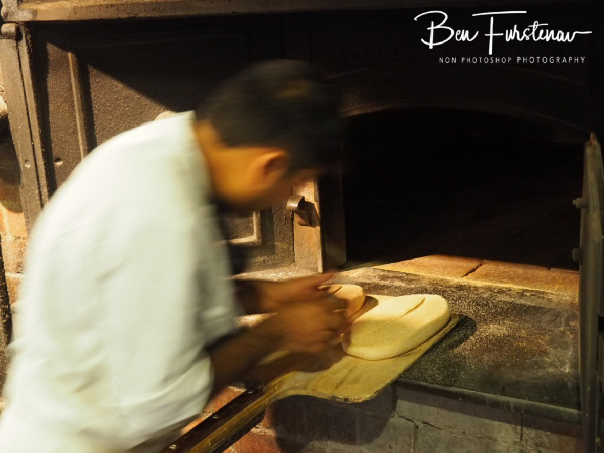 Shailesh swiftly loading the wood fired oven with sourdough bread, Newrybar, New South Wales, Australia