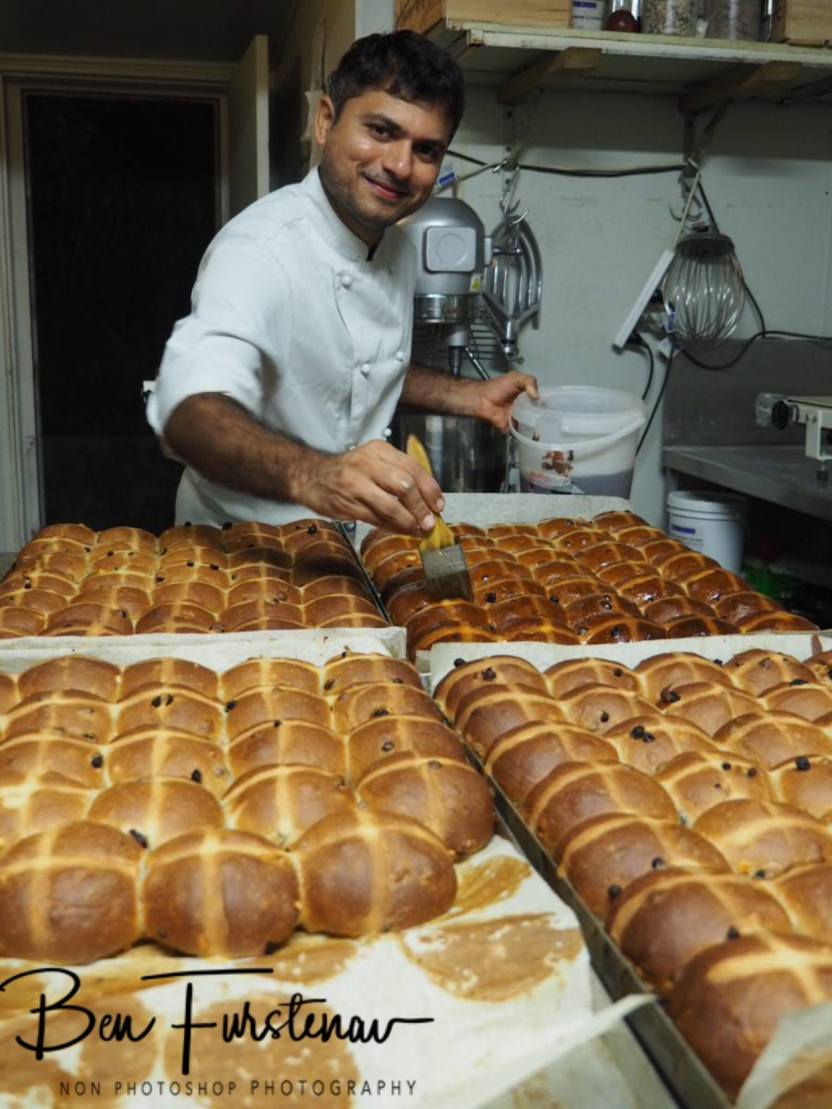 Shailesh glazing hot cross buns, Newrybar, New South Wales, Australia