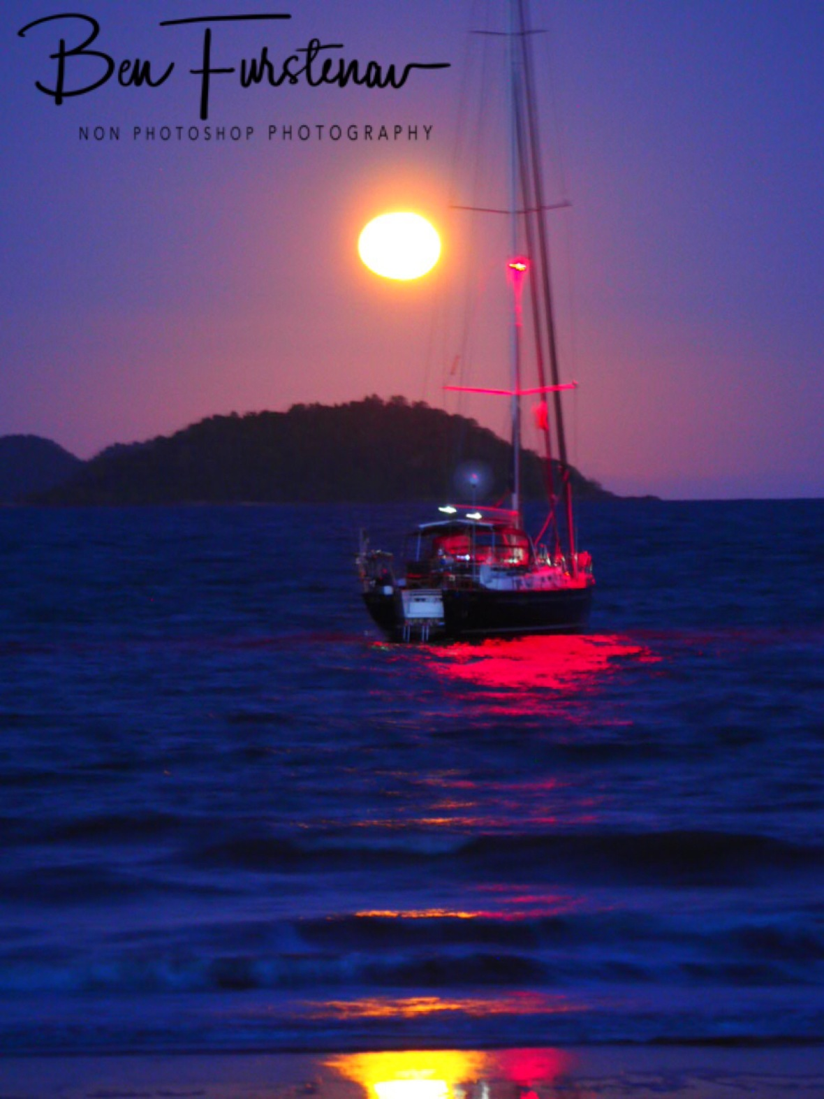 Full moon over anchored yacht at South Mission Beach, Queensland, Australia